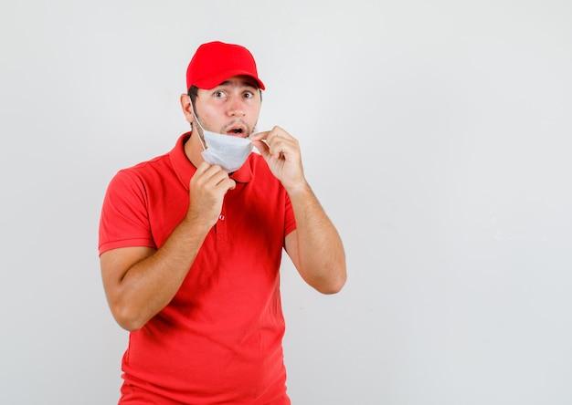 Lieferbote im roten t-shirt, kappe, die maske abnimmt und überrascht aussieht