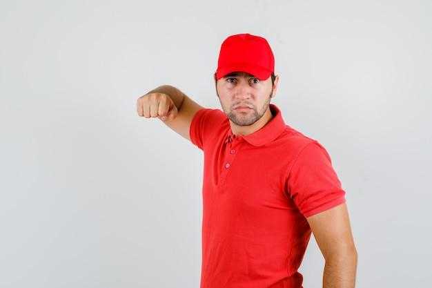 Lieferbote im roten t-shirt, kappe, die mit faust droht und wütend aussieht