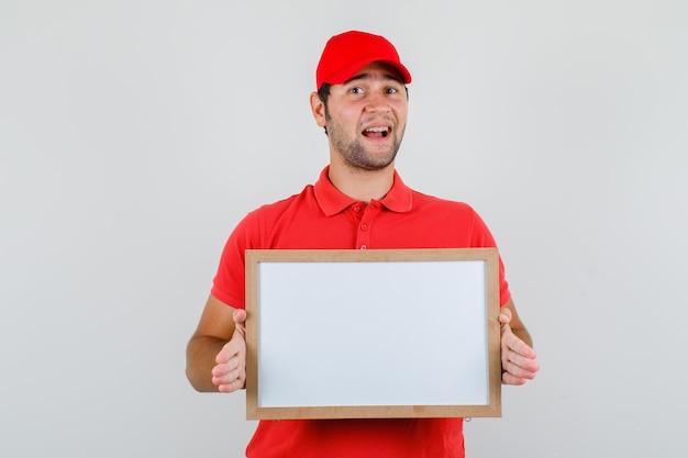 Lieferbote im roten t-shirt, kappe, die weiße tafel hält und fröhlich schaut