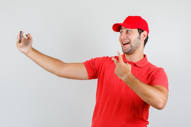 Lieferbote im roten t-shirt, mütze, die selfie mit v-zeichen nimmt und fröhlich schaut