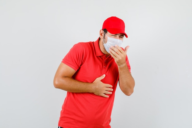 Lieferbote im roten t-shirt, mütze, maske, die unter husten leidet und krank aussieht