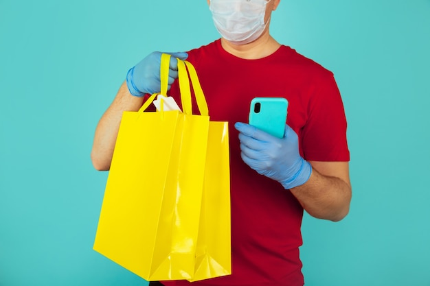Lieferbote im roten t-shurt und in den handschuhen, die gelbe tasche lokalisiert auf blauem hintergrund halten.