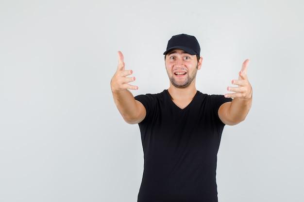 Lieferbote im schwarzen t-shirt, kappe, die einlädt, zu kommen und fröhlich auszusehen