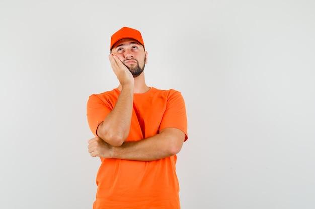 Lieferbote im t-shirt, mütze, die wange auf erhobener handfläche lehnt und nachdenklich aussieht, vorderansicht.