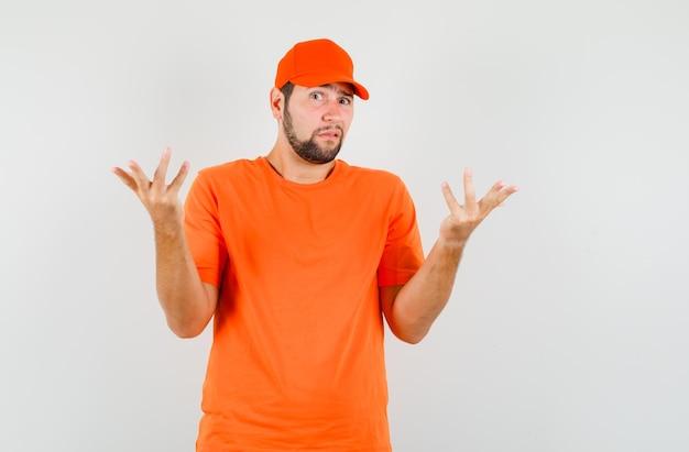 Lieferbote im t-shirt, mütze mit erhobenen händen, die verwirrte geste zeigt, vorderansicht.