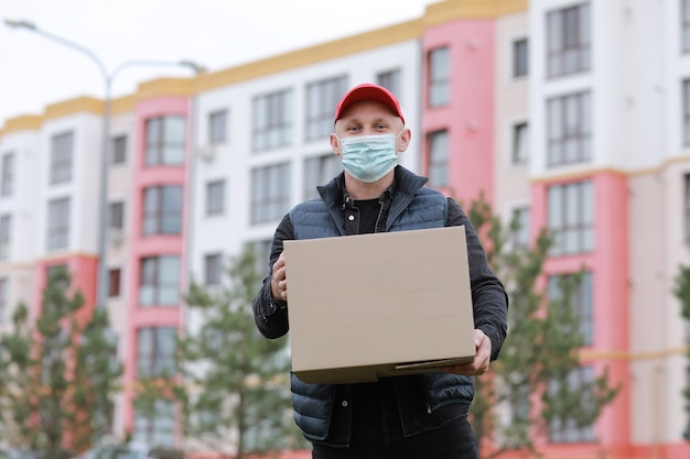 Lieferbote in der roten kappe, gesichtsmaske halten leeren karton draußen