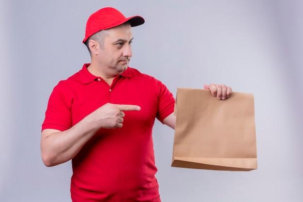 Lieferbote in der roten uniform und in der kappe, die papierpaket hält, das mit zeigefinger darauf zeigt und zur seite schaut mit ernstem gesicht, das über isoliertem weißem raum steht