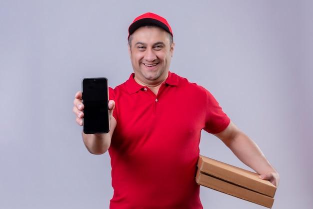Lieferbote in der roten uniform und in der kappe, die pizzaschachteln halten, die sein smartphone lächelnd mit glücklichem gesicht stehend zeigen