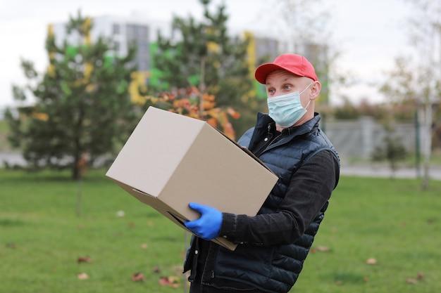 Lieferbote in der weißen kappe des weißen t-shirts einheitliches gesicht medizinische maskenhandschuhe halten leeren karton