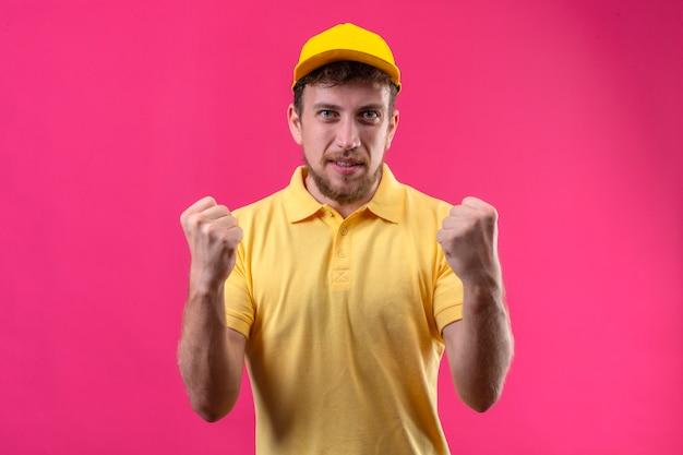 Lieferbote in gelbem poloshirt und mütze sehen aufgeregt aus und freuen sich über seinen erfolg und sieg. er ballte die fäuste vor freude und freute sich, sein ziel und seine ziele auf isoliertem blau zu erreichen