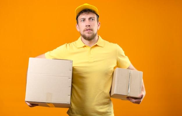 Lieferbote in gelbem poloshirt und mütze stehend mit kartonverpackung und großem karton mit ernstem gesicht ohne lächeln auf orange
