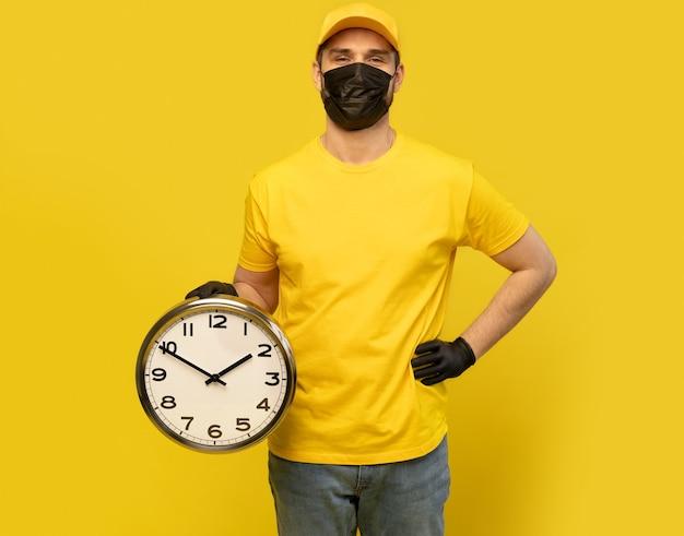 Lieferbote in gelber arbeitskleidung halten uhr isoliert. professioneller männlicher angestellter im mützen-t-shirt-druck, der als kurierhändler arbeitet