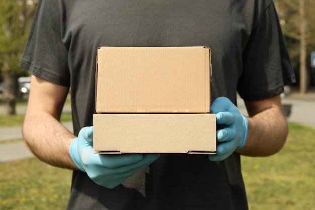 Lieferbote in handschuhen hält leere kisten, platz für text
