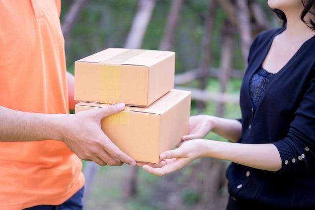 Lieferbote in orange übergibt einer frau pakete