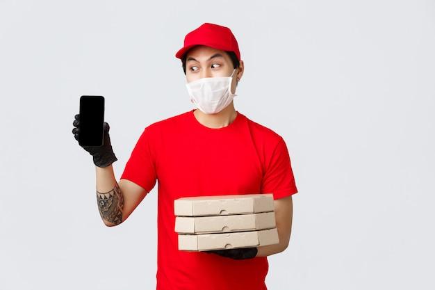 Lieferbote in roter kappe, t-shirt, hält pizzaschachteln und zeigt smartphonebildschirm. asiatischer kurier bestätigt bestellinformationen mit dem kunden, bringt lebensmittel während der quarantäne zu den menschen nach hause und trägt eine medizinische maske