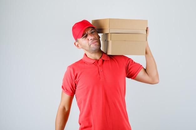 Lieferbote in roter uniform, der pappkartons auf seiner schulter hält und unzufrieden aussieht