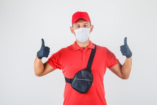 Lieferbote in roter uniform, medizinischer maske, handschuhe mit daumen hoch und positiv aussehend