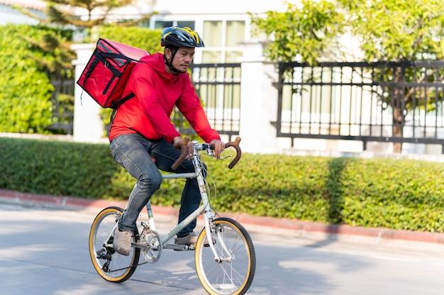 Lieferbote in roter uniform radfahren, um produkte an kunden zu hause zu liefern.