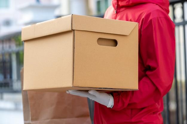 Lieferbote in roter uniform schneller versand von waren an kunden