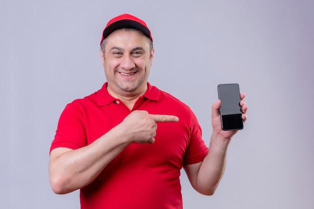 Lieferbote in roter uniform und kappe, die sein smartphone zeigt, das mit zeigefinger darauf zeigt und fröhlich stehend lächelt