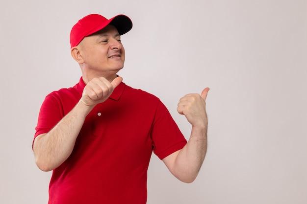 Lieferbote in roter uniform und mütze, der mit selbstbewusstem lächeln zur seite schaut und mit den zeigefingern zur seite zeigt
