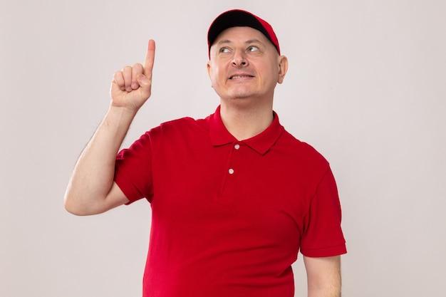 Lieferbote in roter uniform und mütze, die mit einem lächeln auf einem intelligenten gesicht aufschaut, das mit dem zeigefinger nach oben zeigt und eine gute idee hat