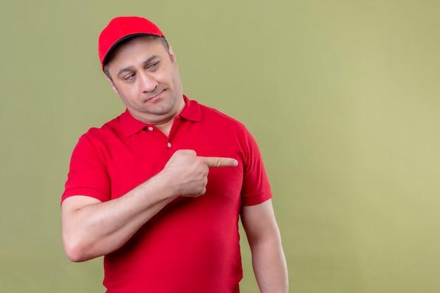 Lieferbote in roter uniform und mütze, die mit skeptischem ausdruck beiseite schauen, der mit zeigefinger zur seite zeigt, die über isoliertem grünraum steht