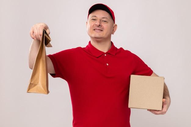 Lieferbote in roter uniform und mütze, die pappschachtel und papierpaket hält und fröhlich lächelt