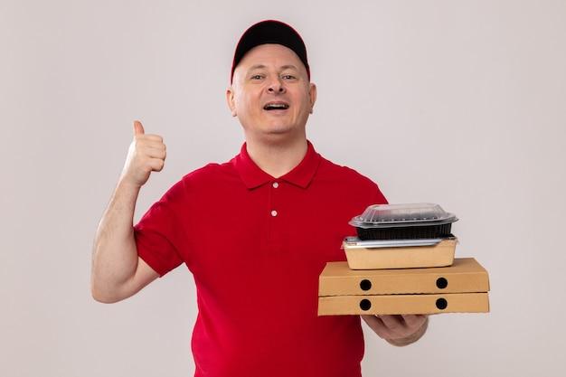 Lieferbote in roter uniform und mütze, die pizzakartons und lebensmittelpakete glücklich und positiv lächelnd hält und nach hinten zeigt, mit dem daumen auf weißem hintergrund white