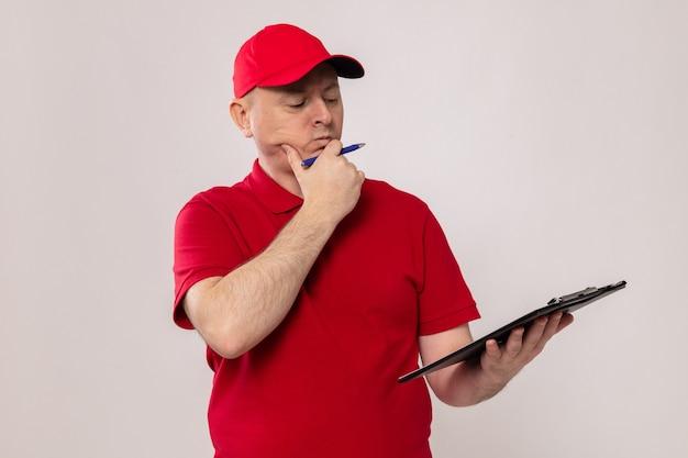 Lieferbote in roter uniform und mütze, die zwischenablage mit stift hält und die zwischenablage mit nachdenklichem ausdruck betrachtet