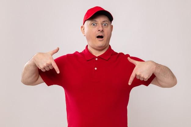 Lieferbote in roter uniform und mütze mit blick auf die kamera überrascht und zeigt mit den zeigefingern nach unten, die auf weißem hintergrund stehen