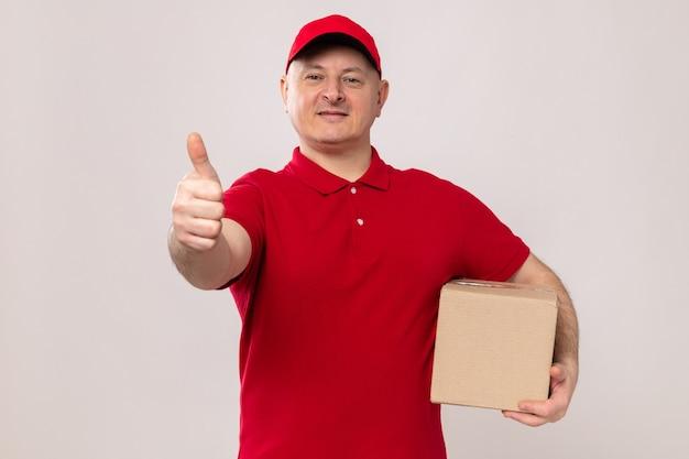 Lieferbote in roter uniform und mütze mit karton, der in die kamera schaut und selbstbewusst lächelt und daumen nach oben auf weißem hintergrund zeigt