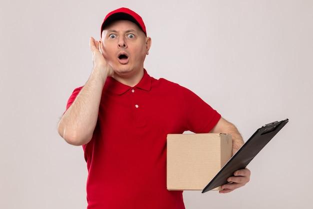 Lieferbote in roter uniform und mütze mit karton und klemmbrett, die erstaunt und überrascht aussieht