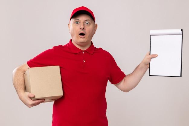 Lieferbote in roter uniform und mütze mit karton und klemmbrett mit leeren seiten, die erstaunt und überrascht aussehen looking