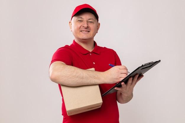 Lieferbote in roter uniform und mütze mit karton und klemmbrett mit stift, der sich notizen macht und selbstbewusst lächelt