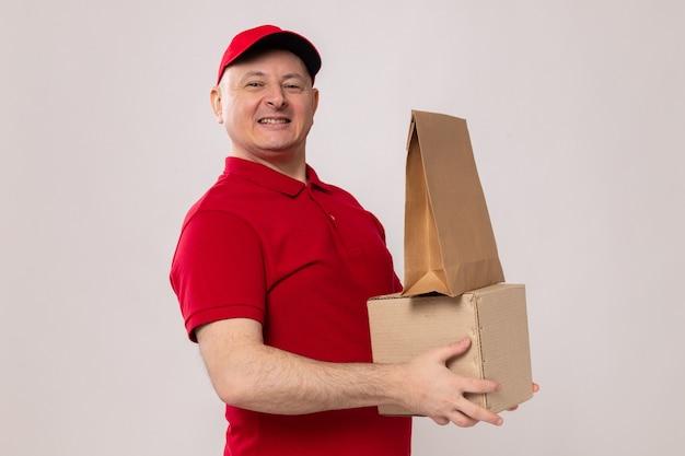 Lieferbote in roter uniform und mütze mit karton und papierpaket posiert lächelnd selbstbewusst glücklich und positiv