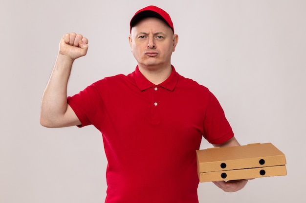 Lieferbote in roter uniform und mütze mit pizzakartons, die mit ernstem, selbstbewusstem ausdruck aussehen und die faust wie ein gewinner heben