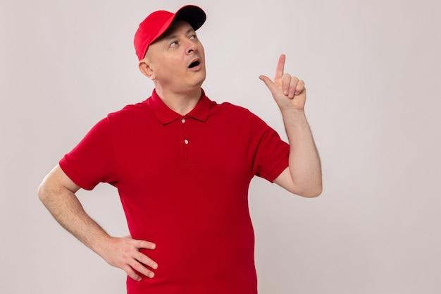 Lieferbote in roter uniform und mütze schaut glücklich und überrascht auf und zeigt zeigefinger mit neuer idee having