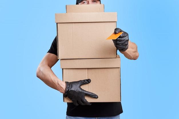 Lieferbote in schwarzer uniform mit medizinischen handschuhen und schutzmaske halten pappkarton