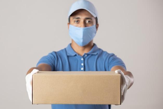 Lieferbote in uniform, der sich mit handschuhen und masken in quarantäne schützt