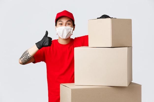 Lieferbote in uniform, medizinischer maske und handschuhen, die in der nähe von stapel von verpackungsschachteln stehen, zeigen den daumen nach oben in der genehmigung und garantieren einen schnellen und sicheren lieferservice