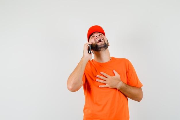 Lieferbote lacht beim telefonieren mit dem handy in orangefarbenem t-shirt, mütze, vorderansicht.