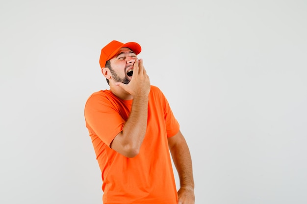 Lieferbote lacht mit der hand auf den mund im orangefarbenen t-shirt, mütze, vorderansicht.