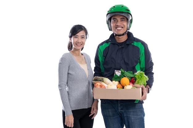 Lieferbote liefern lebensmittelbestellung an kunden isoliert über weißem hintergrund