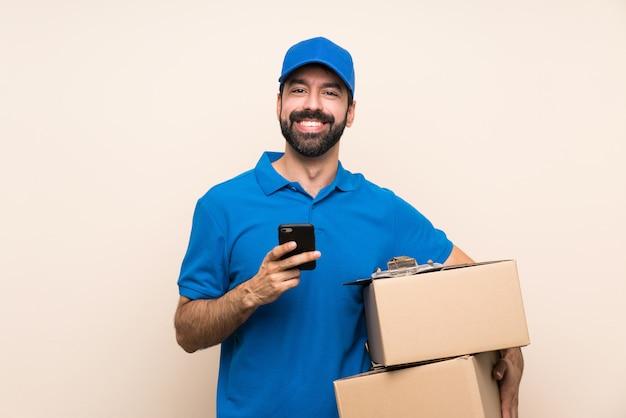 Lieferbote mit bart über dem lokalisierten senden einer mitteilung mit dem mobile