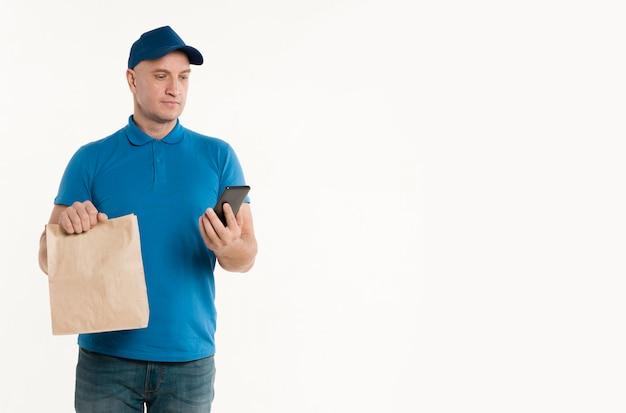 Lieferbote mit der papiertüte, die smarthpone betrachtet