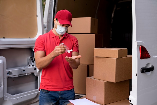 Lieferbote mit maske mit händedesinfektionsmittel