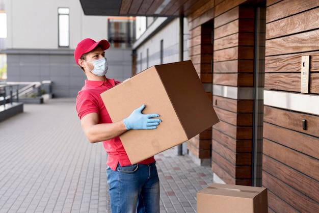 Lieferbote mit maske und handschuhen