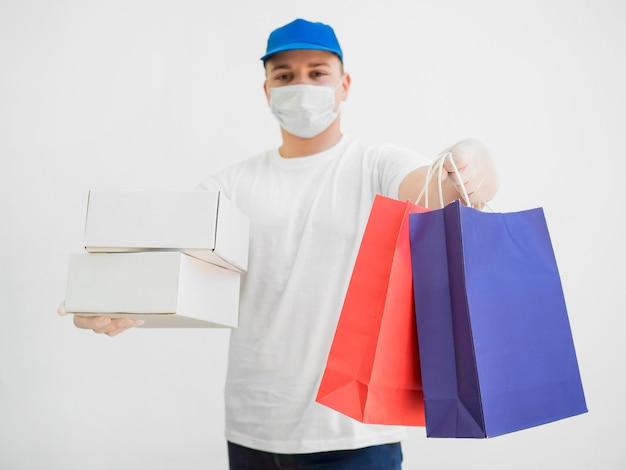 Lieferbote mit maske und taschen