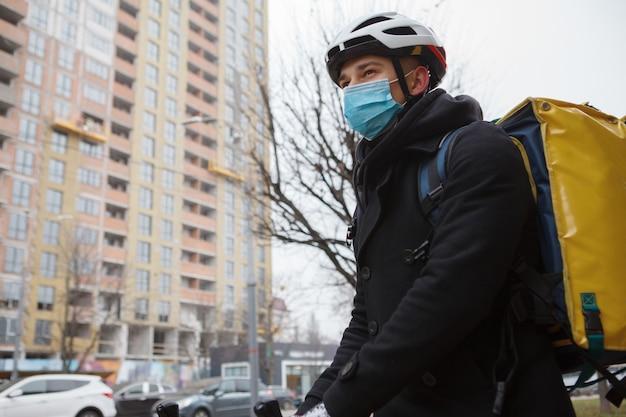 Lieferbote mit medizinischer maske, die im herbst oder winter in der stadt spazieren geht